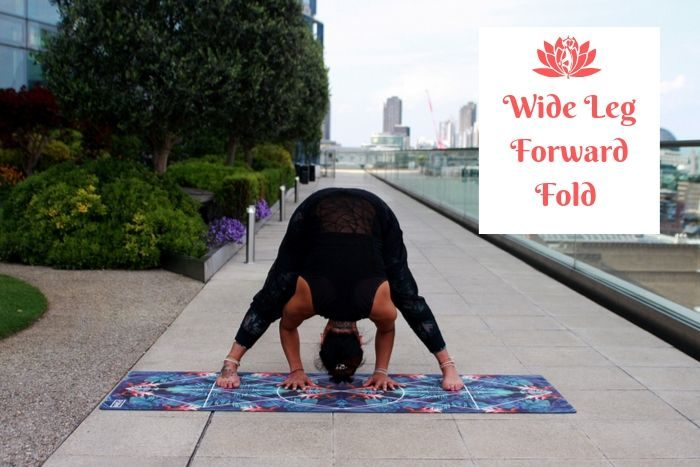a man holding the yoga detox position of the wide leg forward fold with a city panorama in the background