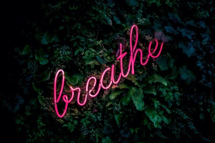 a pink neon sign spelling the word breath with greenery in the background
