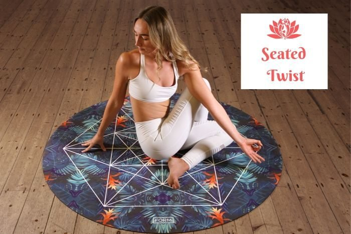 a slender blonde haired woman performing the seated twist on a yoga mat
