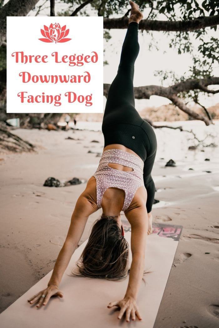 a woman  holding the yoga position three legged downward facing dog on a beach