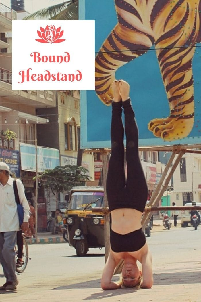 a blonde woman in black workout clothes performing a yoga bound headstand in the streets of Mumbai