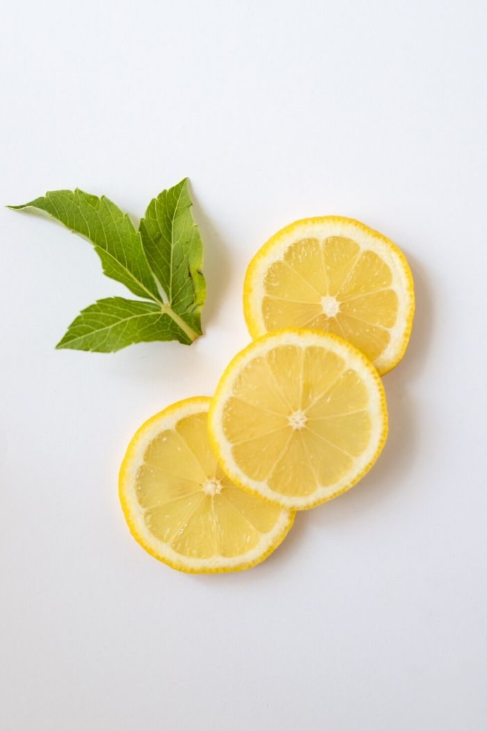 three slices of lemon and some mint leaves against a white background