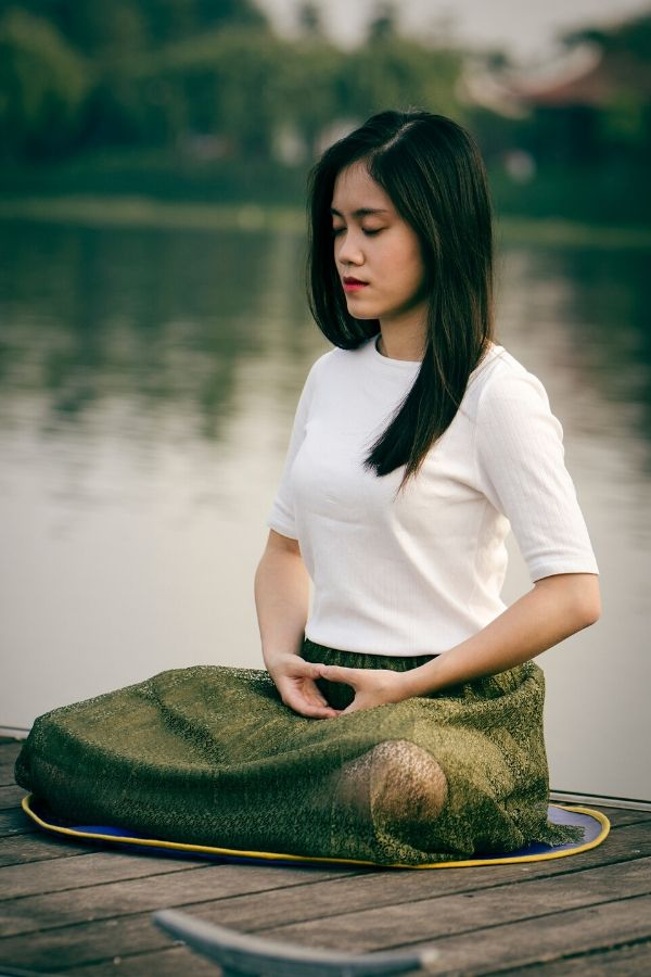 a young Asian woman meditating sitting in the lotus position on the pier of a lake
