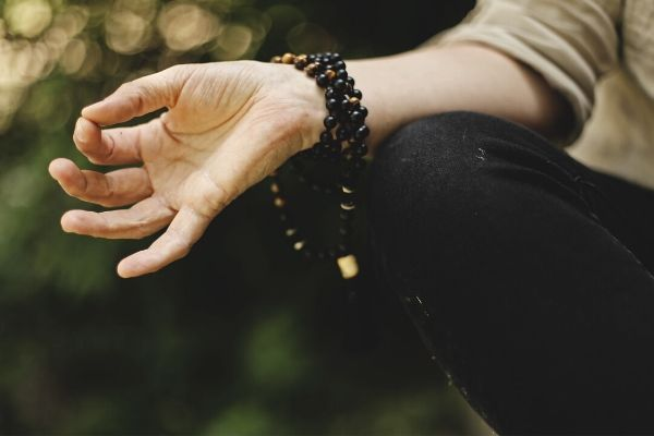 a hand in the gyan meditation hand gesture with prayer beads wrapped around the wrist