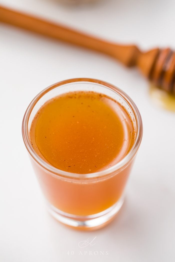 Close up of an apple cider vinegar shot on a white background