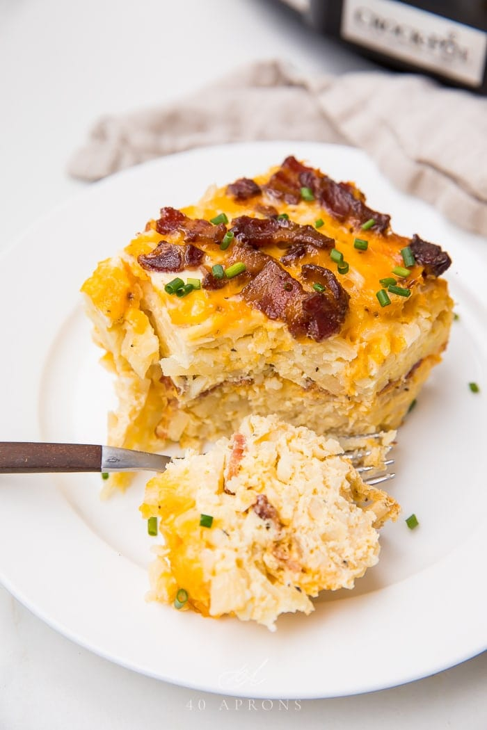 A square of breakfast casserole on a white plate with a slice cut off
