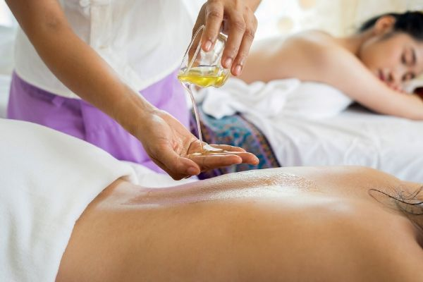 a massage therapist pouring some oil over her hand onto a clients back to give a detox massage