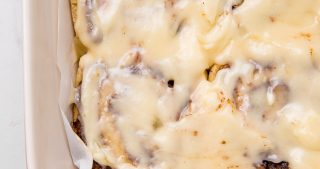 Gluten free cinnamon rolls in a baking pan with cream cheese frosting