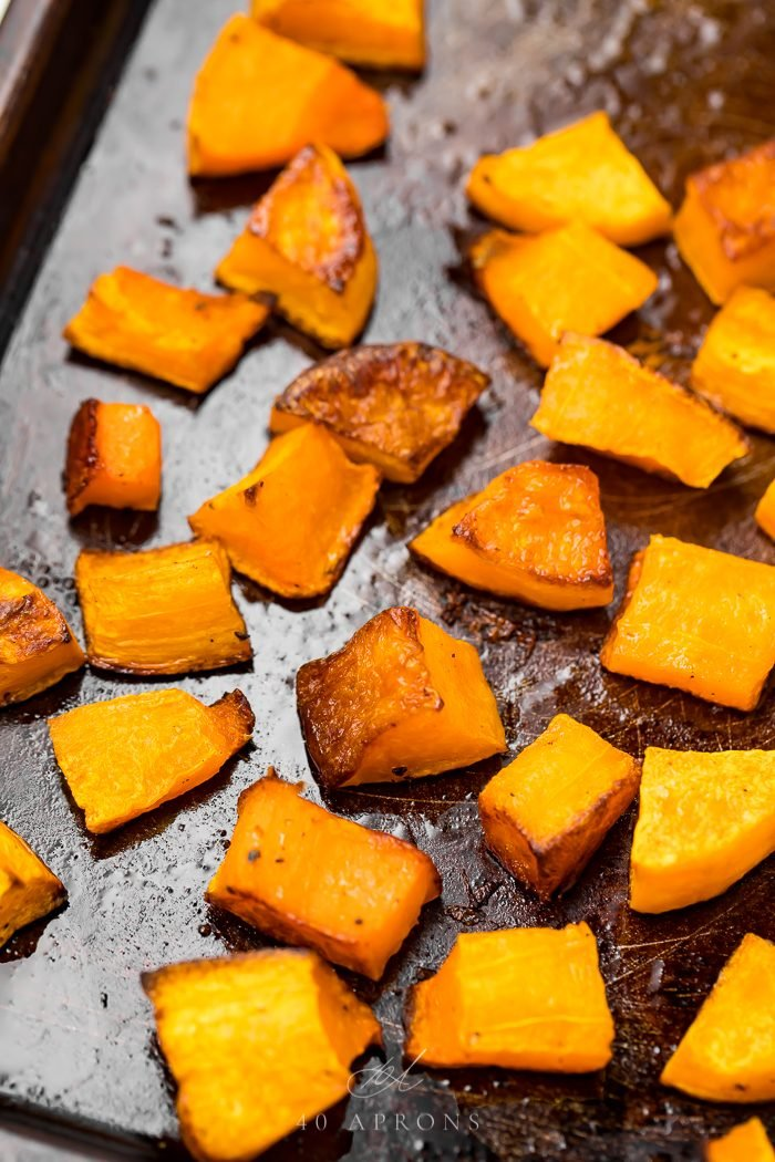 Cubes of baked butternut squash on a baking sheet