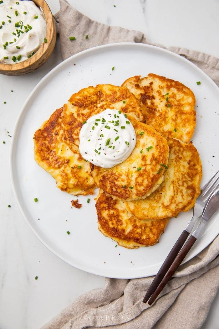 Leftover mashed potato pancakes on a white plate with a knife and fork