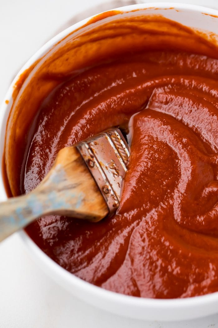 A bowl of Whole30 bbq sauce with a brush in it