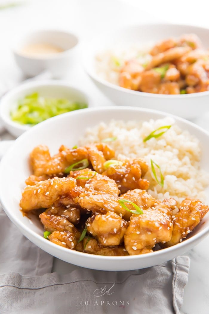 Sesame chicken served in a white bowl with cauliflower rice