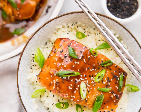 Whole30 teriyaki salmon over cauliflower rice in a bowl with chopsticks