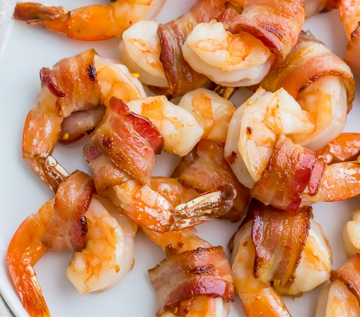 Bacon wrapped shrimp on a white plate