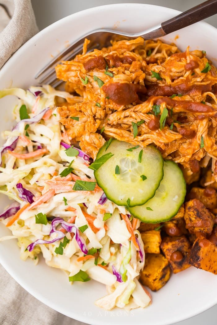 Close up of BBQ chicken bowl with sweet potatoes and coleslaw