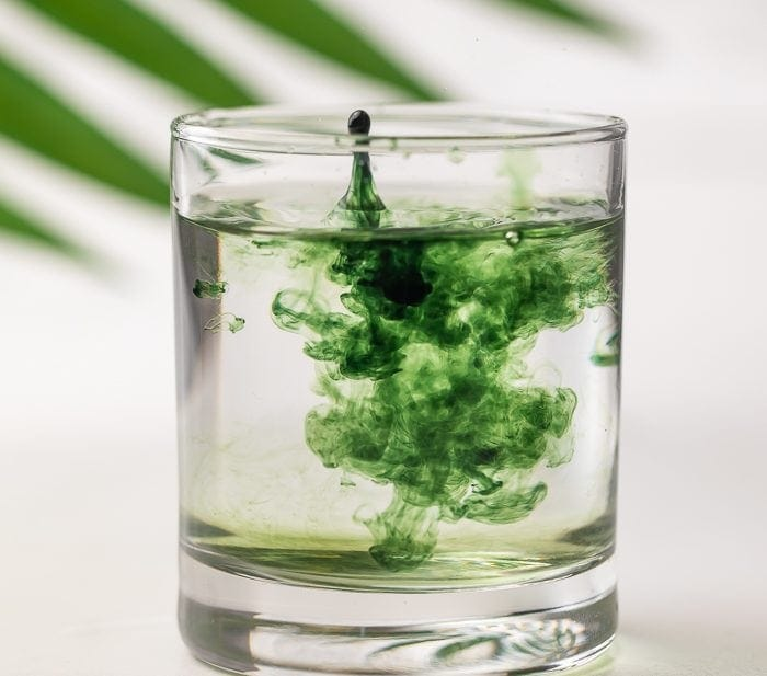 Liquid chlorophyll being dropped into a glass of water