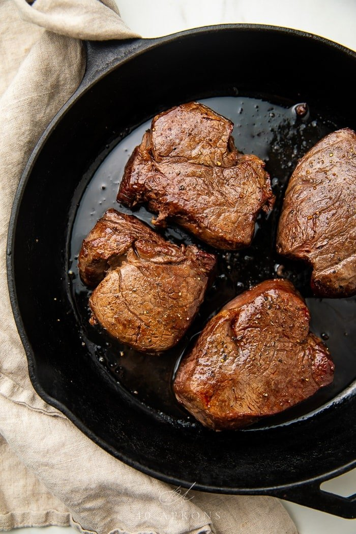 four filet mignons in cast iron skillet