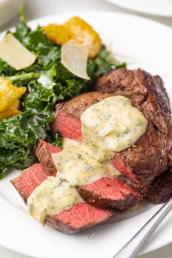 medium rare filet mignon with bearnaise sauce on white plate with kale Caesar salad