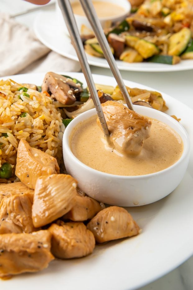 hibachi chicken being dipped in mustard sauce with chopsticks
