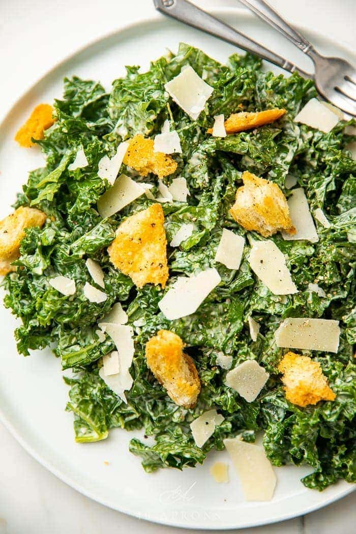 Kale caesar salad on a white plate with croutons