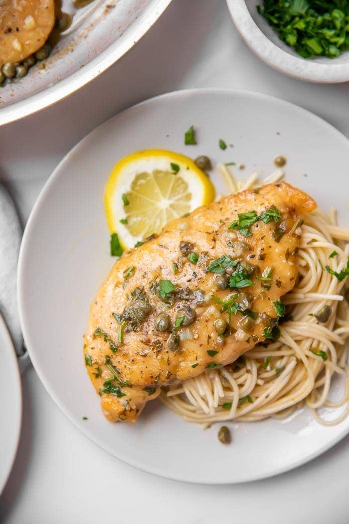 Chicken piccata served over pasta on a white plate
