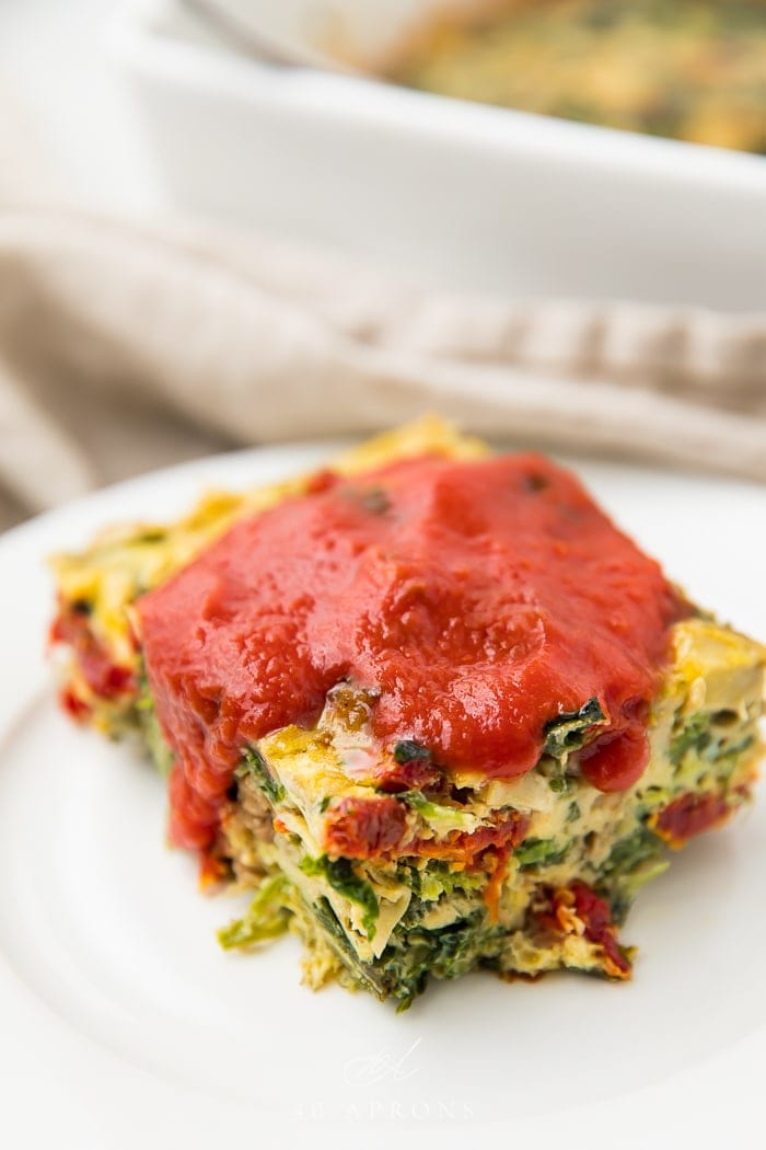 Italian breakfast casserole served on a white plate with red sauce