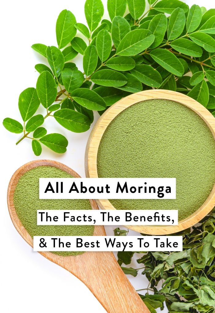 Powdered moringa in a bowl and spoon and moringa leaves
