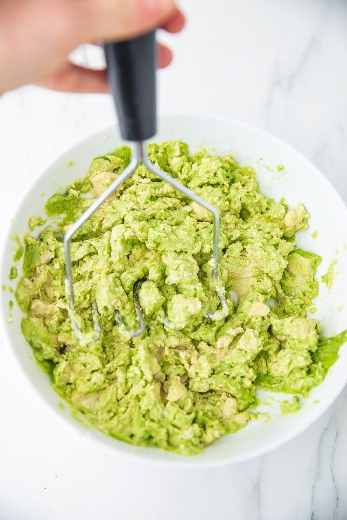 Smashing avocados with potato masher