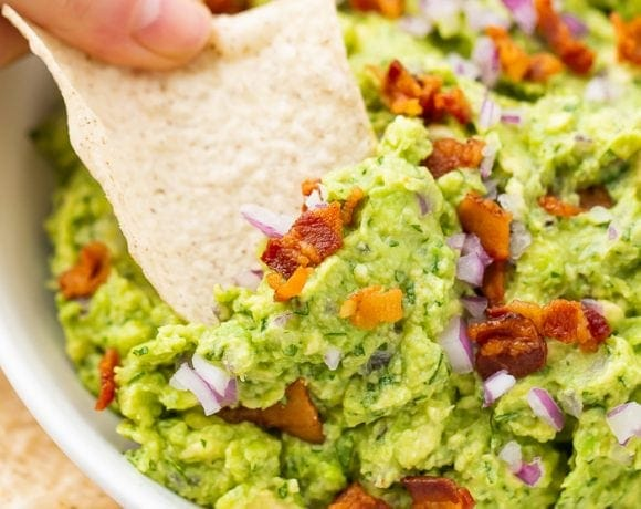 Bowl of bacon guacamole with a tortilla chip being dipped in