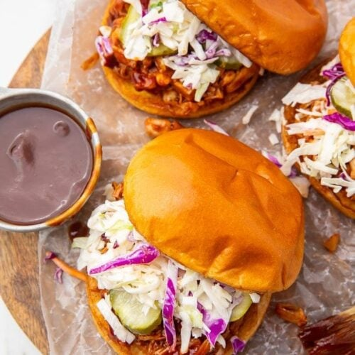 Three vegan BBQ jackfruit sandwiches with a side of barbecue sauce