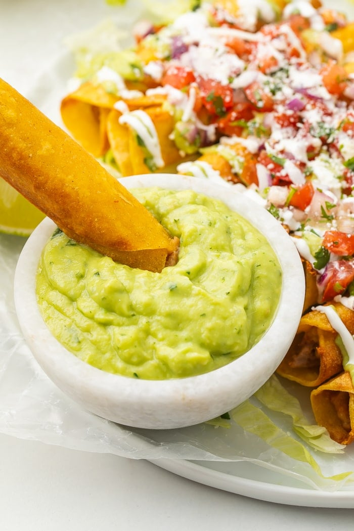 Bean and cheese taquito being dipped in avocado salsa
