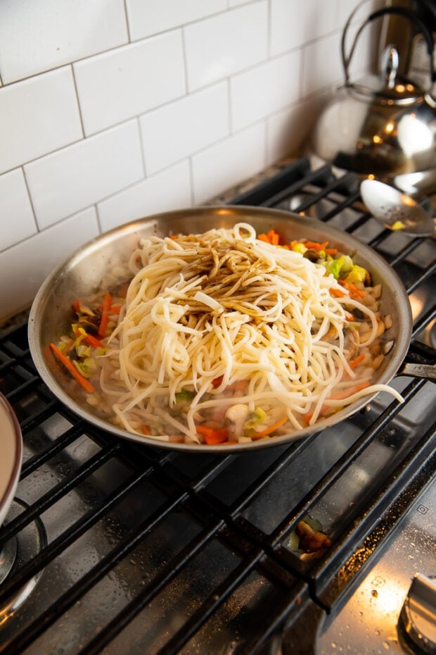 Palmini noodles on top of chicken and veggies in a large wok on a gas stove