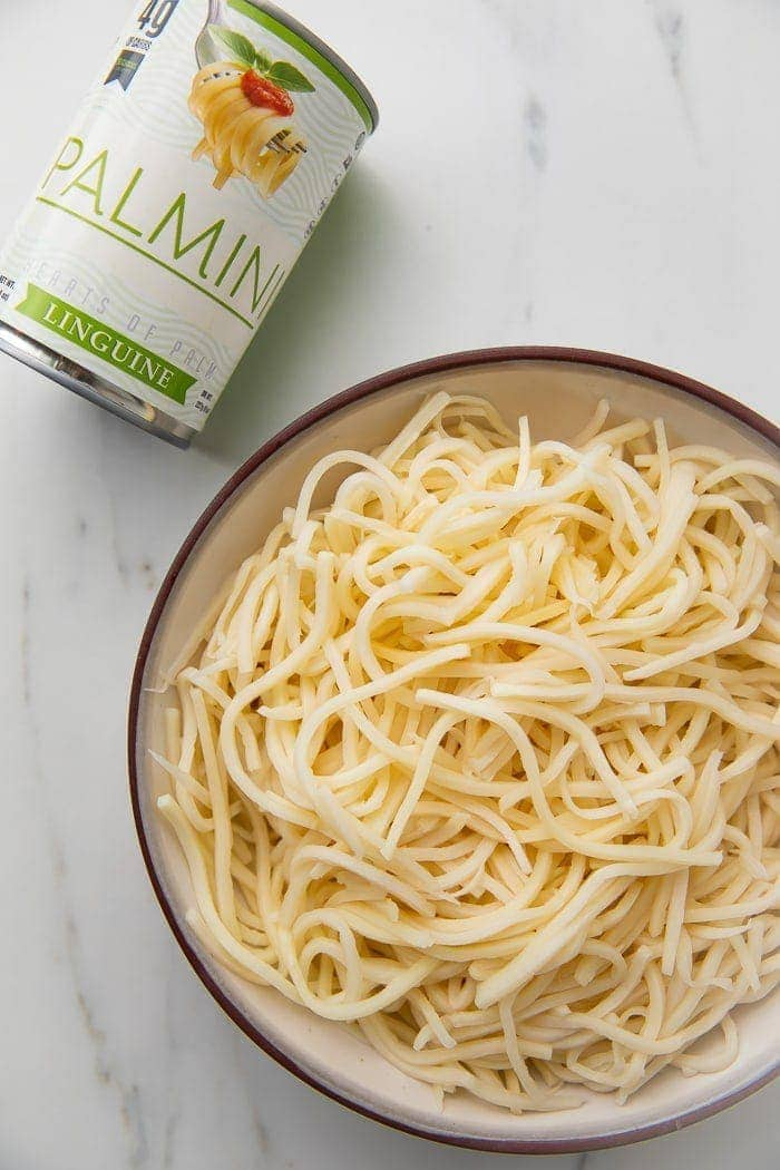 Bowl of palmini noodles next to a can of palmini