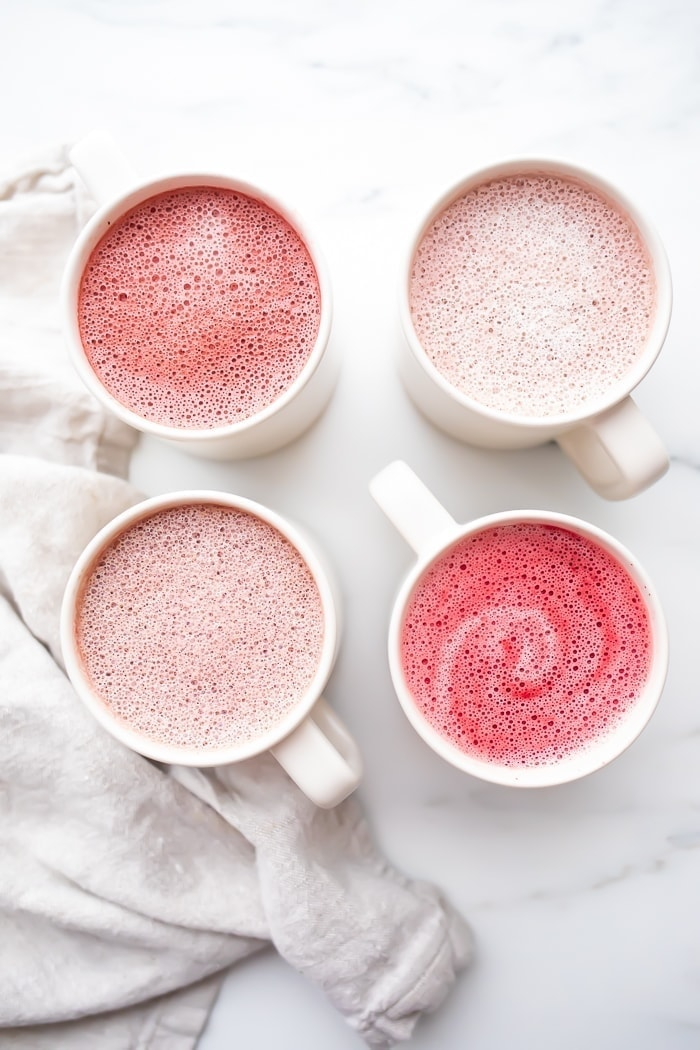Four pink lattes in white mugs