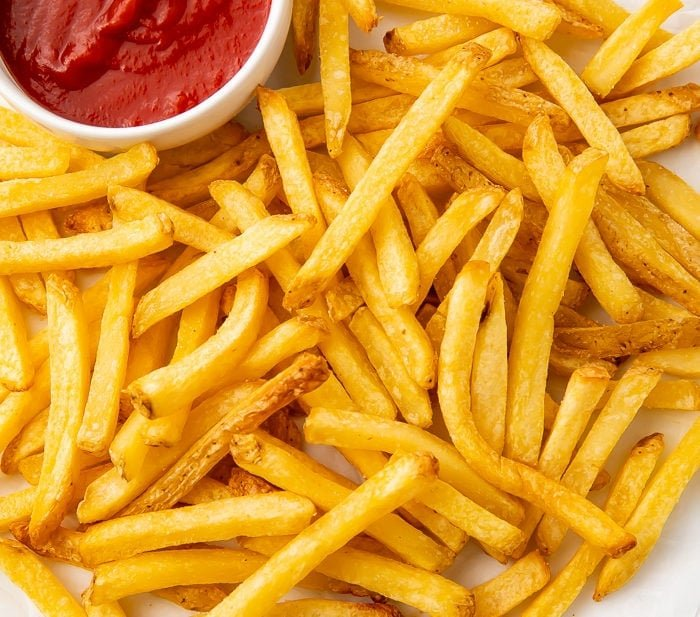 Air fryer french fries on a white plate with a side of ketchup