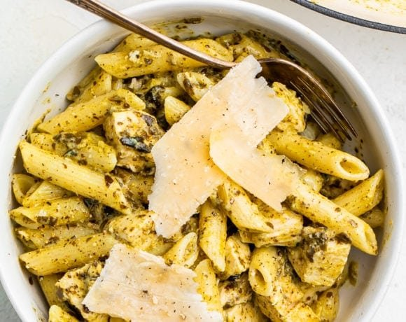 One-pot chicken pesto pasta in a bowl topped with Parmesan cheese