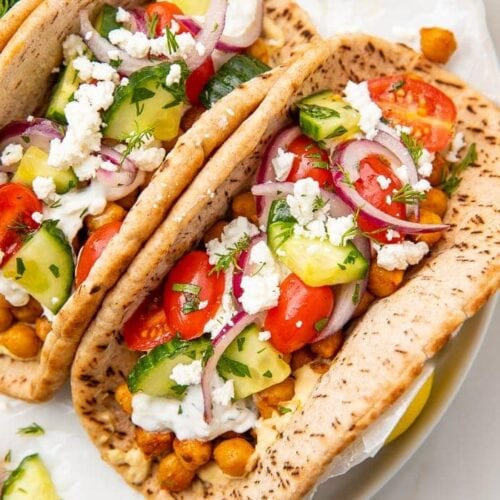 Two chickpea gyros on a white plate