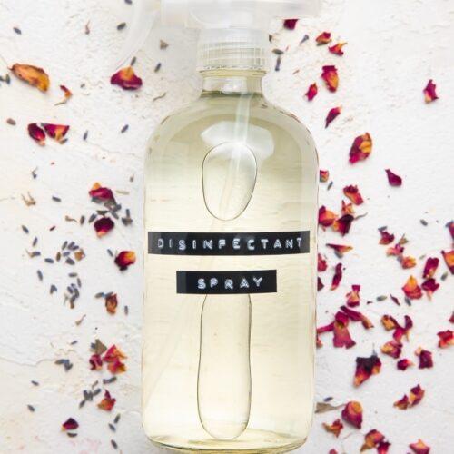 Spray bottle of DIY Lysol spray on dried rose petals