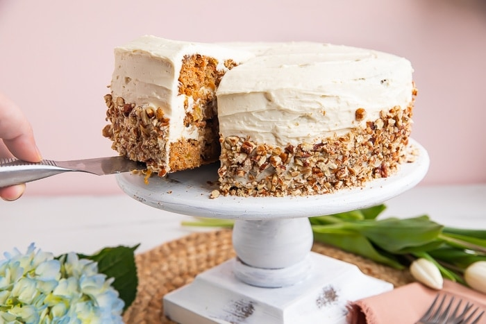Paleo carrot cake on a cake stand with a piece being lifted out