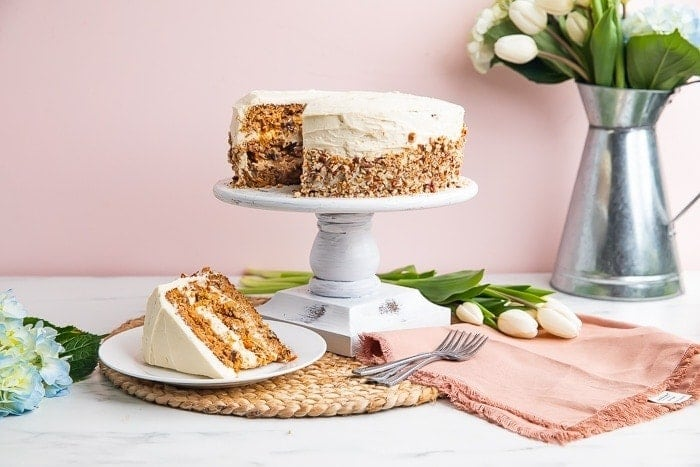 Carrot cake on cake stand next to spring decorations