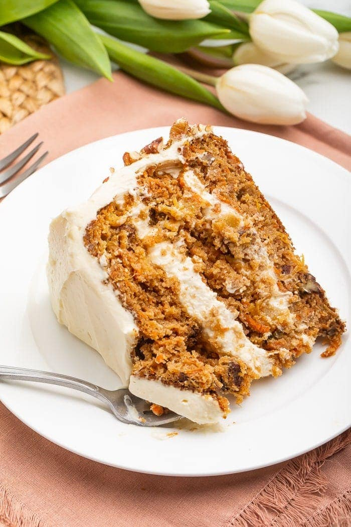 Slice of paleo carrot cake on a white plate with a fork