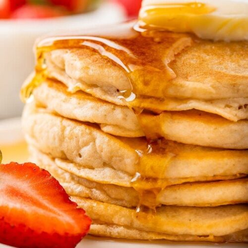Syrup being poured on a stack of fluffy gluten-free pancakes