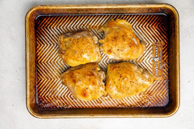 Cooked chicken thighs on a baking sheet