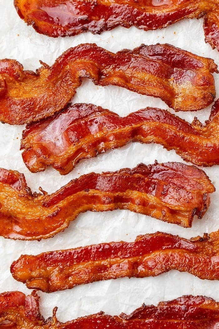 Overhead shot of slices of crispy, cooked bacon on parchment paper