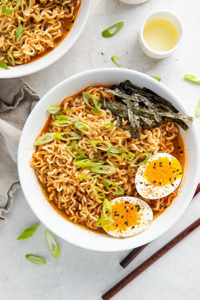 Spicy ramen in a bowl with chopsticks and a glass of sake