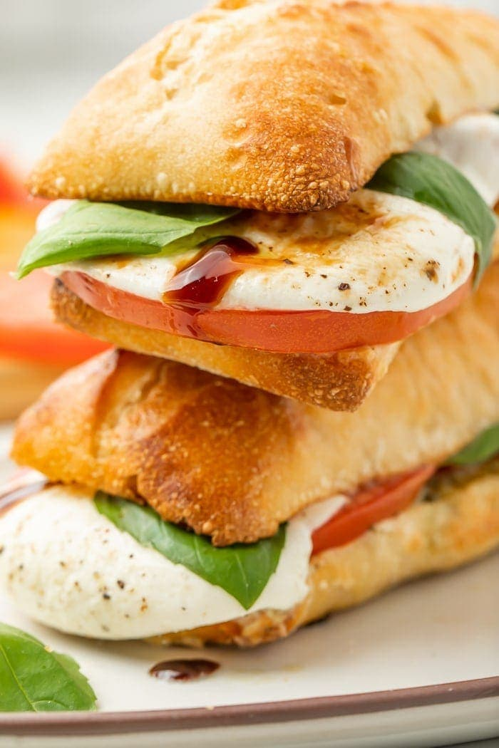 Two halves of a caprese sandwich with one on top of the other