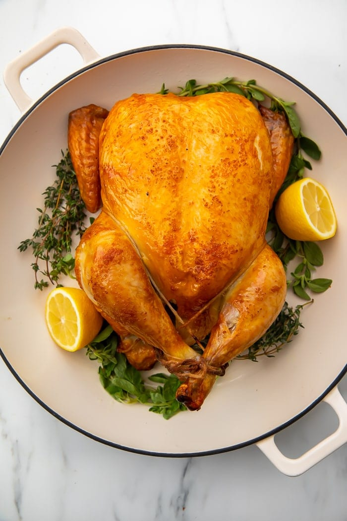 Chicken brine on a whole chicken on a plate with lemons and herbs