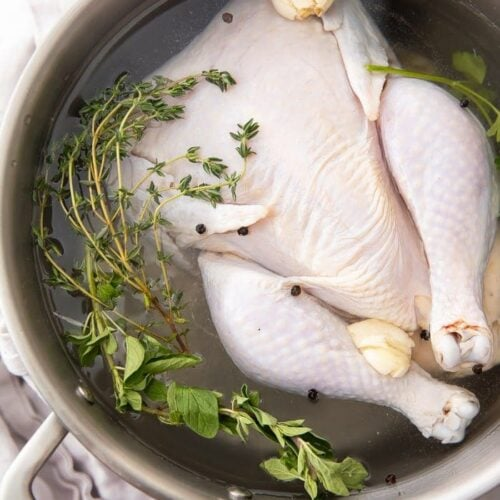 A whole chicken in a pot of brine