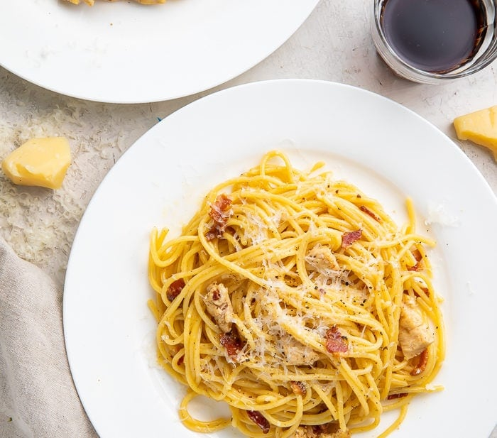 Chicken carbonara on a plate with a glass of red wine