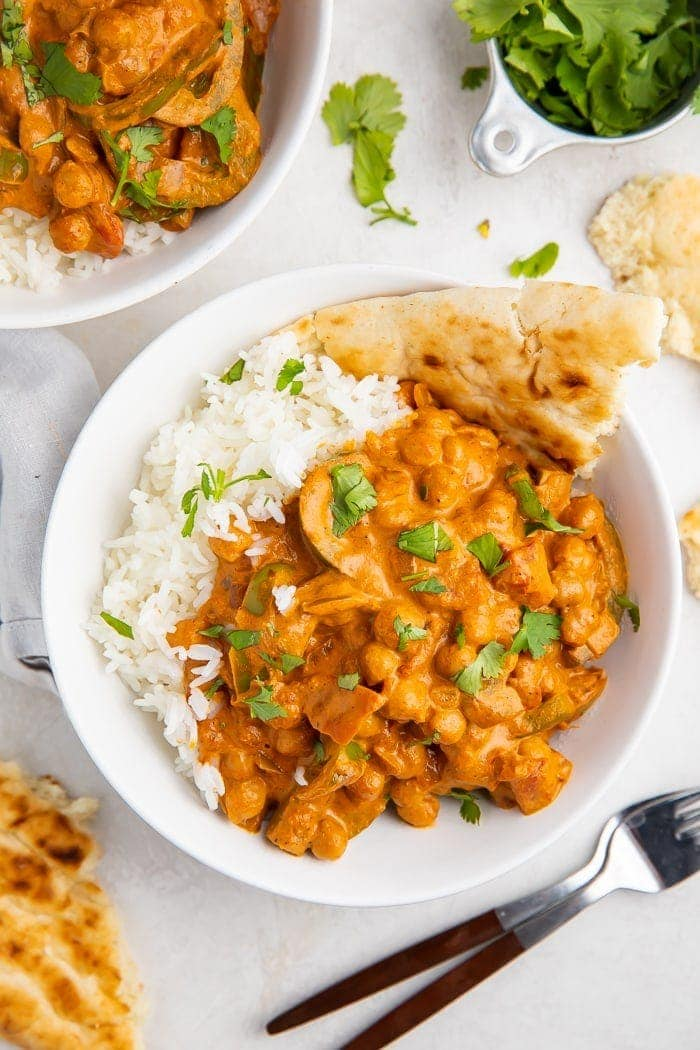 Bowls of chickpea tikka masala with naan